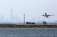 An aircraft takes off from New York's John F Kennedy Airport against a hazy backdrop of the New York sklyine, May 25, 2015. An Air France flight 22 jet was escorted into the airport by military aircraft after threats were made against the flight. AFP PHOTO/ Trevor Collens