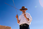 A man uses divining rods to locate an underground opal seam.  Coober Pedy, South Australia, AUSTRALIA.