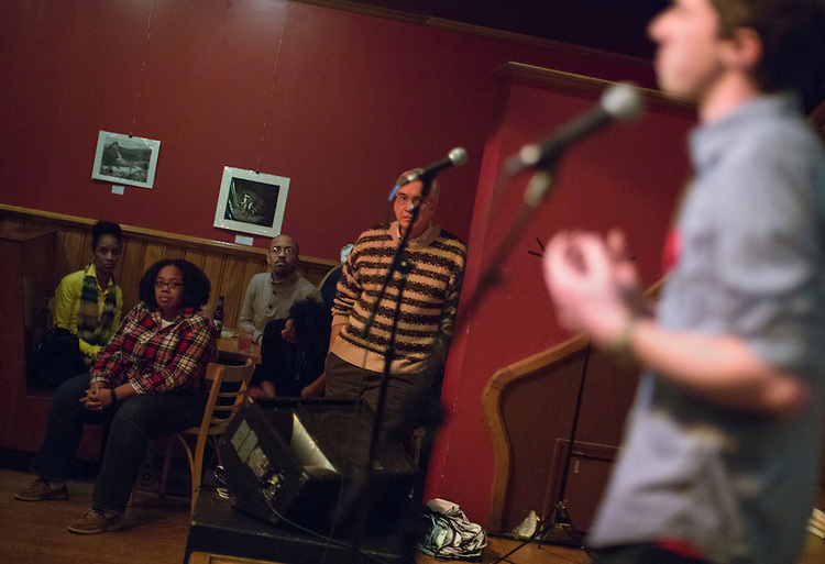 Ohio University student Jacob Chaffin performs during a social justice-themed open mic night at Casa Nueva in Athens on January, 21, 2014. Watching the performance, from left, are Stephanie Sanders, Lisa Harrison, Gerard Grigsby, Chanel Glover, and John Schmieding. Photo by Lauren Pond