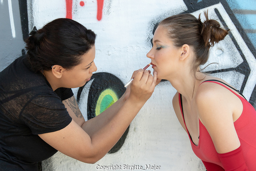 Make-up artist Jacqueline Silva, making the female model ready for the photo shoot. Model wearing red tricot, shot in profile with colorful wall as backdrop