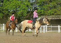 Mädchen beim Reitunterricht auf Ponyhof, Mädchen reiten im Trab-Tempo auf ihren Reitponys auf dem Reitplatz, Reiten, Reiterhof, Gestüt
