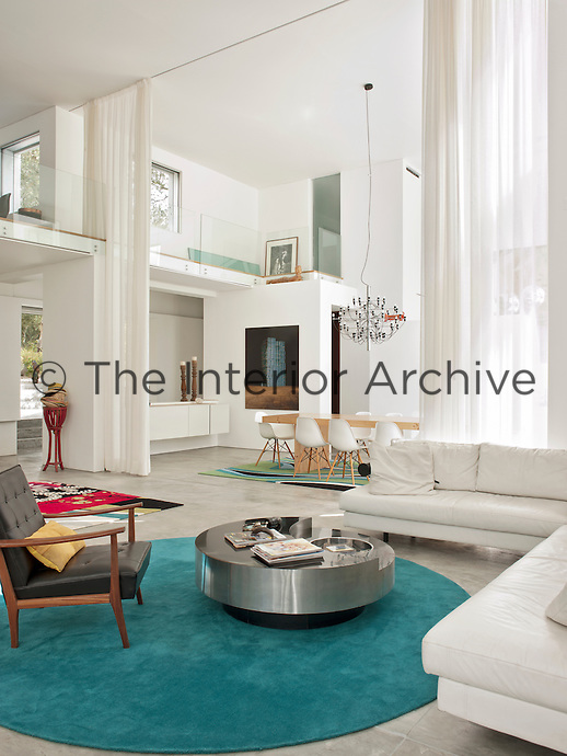 An inspiring, open plan living and dining space with a double height ceiling. A white leather sofa from B&B Italia, a Willy Rizzo coffee table, a Nordic retro armchair stand on a vibrant turquoise carpet by Carpet Diem.