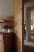 An open wooden door made from the same wood as the kitchen units leads to a bathroom and bedroom beyond