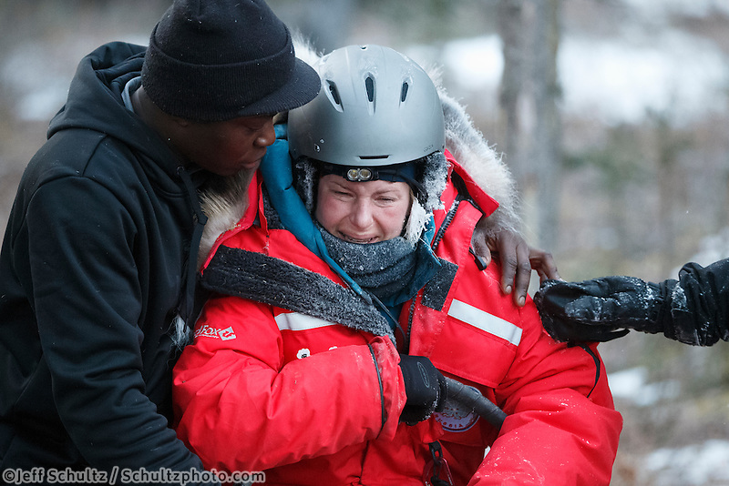 Newton Marshall hugs and comforts Yvonne Dabakk after her ride down the Dalzell Gorge and arrives in Rohn on Tuesday March 4 during Iditarod 2014 . PHOTO BY JEFF SCHULTZ/IDITARODPHOTOS.COM  USE ONLY WITH PERMISSION