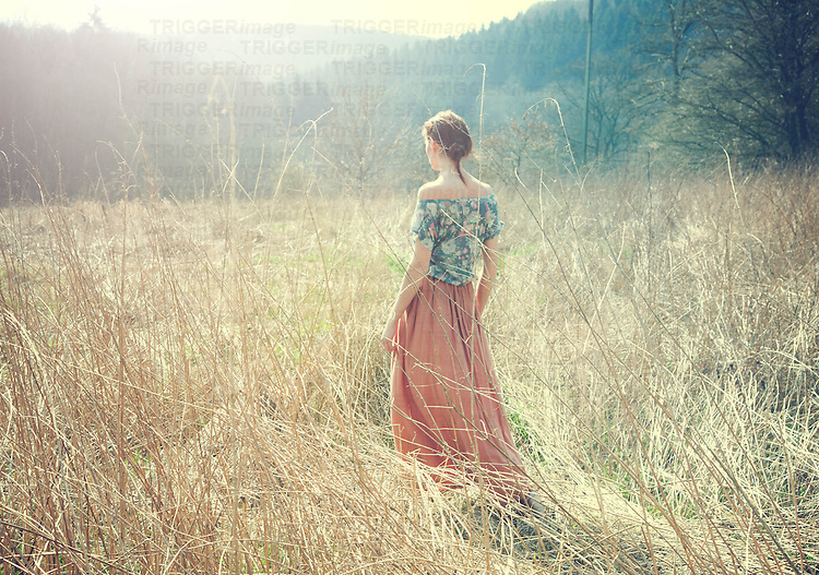 woman in the forest waiting wearing a long dress