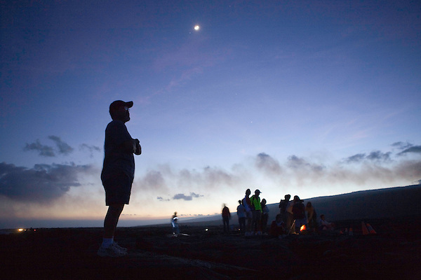 Visitors to Volcanoes National Park watch a nighttime lava flow. Photo by Kevin J. Miyazaki/Redux