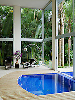 The swimming pool and pinus wood deck extend into the living area where a pair of Le Corbusier chaises seem immersed in the lush garden