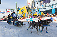 Paige Drobny and team leave the ceremonial start line with an Iditarider at 4th Avenue and D street in downtown Anchorage, Alaska on Saturday March 2nd during the 2019 Iditarod race. Photo by Brendan Smith/SchultzPhoto.com
