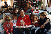 Camp David, Maryland - December 24, 1991 -- United States President George H.W. Bush reads a Christmas story to his grandchildren, Pierce Bush, Marshall Bush, Barbara Bush (daughter of George W. Bush), Lauren Bush, Jenna Bush (daughter of George W. Bush), Ashley Bush and Sam LeBlonde at Camp David in Maryland on Christmas Eve, December 24, 1991..Credit: White House via CNP