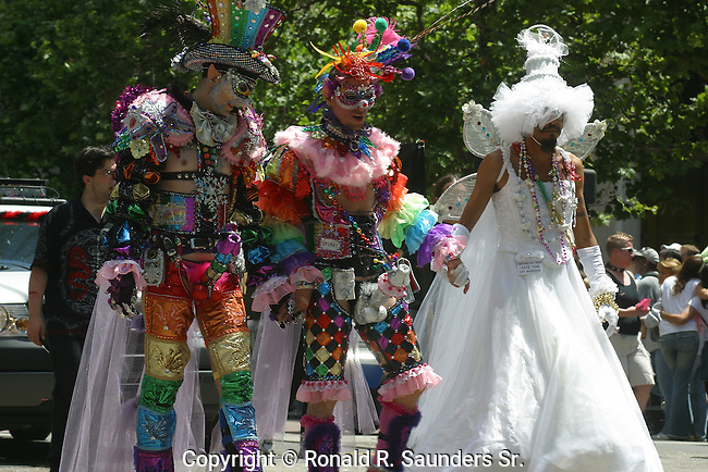 THREE PARADE MARCHERS,GAILY DRESSED,HOLD HANDS as THEY MARCH <br /> DURING the GAY PRIDE PARADE<br /> (8)