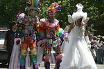 THREE PARADE MARCHERS,GAILY DRESSED,HOLD HANDS as THEY MARCH <br />
