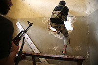 Photographer: Rick Findler..06.10.12 Members of the Free Syrian Army move through man made tunnels between buildings to avoid sniper fire from President Assad's regime n the city of Aleppo, Syria.