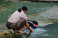 Woman washing clothes in the Yulong River, Yangshuo, Guangxi, China.