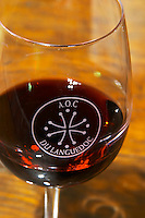 Glass embossed marked with AOC Languedoc and the Languedocian Cathar cross Chateau la Voulte Gasparets. In Gasparets village near Boutenac. Les Corbieres. Languedoc. France. Europe.