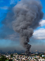 A very large and high plume of smoke from a large fire rises over Manila, Philippines