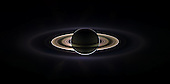 Pasadena, CA - October 11, 2006 -- With giant Saturn hanging in the blackness and sheltering Cassini from the sun's blinding glare, the spacecraft viewed the rings as never before, revealing previously unknown faint rings and even glimpsing its home world.  This marvelous panoramic view was created by combining a total of 165 images taken by the Cassini wide-angle camera over nearly three hours on September 15, 2006. The full mosaic consists of three rows of nine wide-angle camera footprints; only a portion of the full mosaic is shown here. Color in the view was created by digitally compositing ultraviolet, infrared and clear filter images and was then adjusted to resemble natural color. The mosaic images were acquired as the spacecraft drifted in the darkness of Saturn's shadow for about 12 hours, allowing a multitude of unique observations of the microscopic particles that compose Saturn's faint rings.  Ring structures containing these tiny particles brighten substantially at high phase angles: i.e., viewing angles where the sun is almost directly behind the objects being imaged.  During this period of observation Cassini detected two new faint rings: one coincident with the shared orbit of the moons Janus and Epimetheus, and another coincident with Pallene's orbit. The narrowly confined G ring is easily seen here, outside the bright main rings. Encircling the entire system is the much more extended E ring. The icy plumes of Enceladus, whose eruptions supply the E ring particles, betray the moon's position in the E ring's left-side edge. Interior to the G ring and above the brighter main rings is the pale dot of Earth. Cassini views its point of origin from over a billion kilometers (and close to a billion miles) away in the icy depths of the outer solar system. Small grains are pushed about by sunlight and electromagnetic forces. Hence their distribution tells much about the local space environment.  A second version of the mosaic view is presented here in which