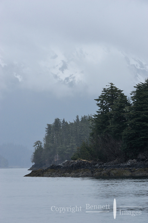 The Chugach Mountains loom out of the clouds on a rainy spring day near Port Gravina, Prince William Sound, Southcentral Alaska, in early May.