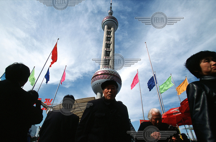 A visitor outside the Oriental Pearl Tower, the tallest in China.