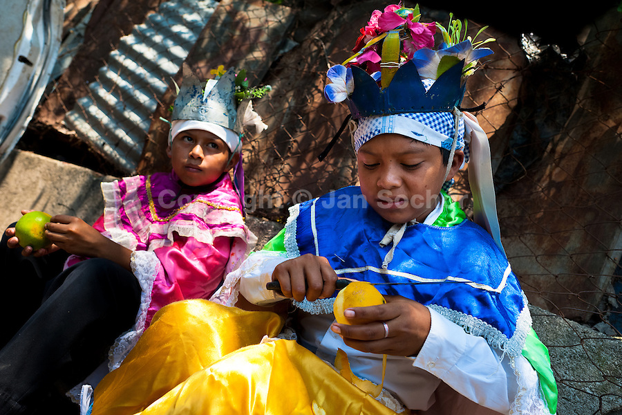 "Salvadoran boys, dressed as Moors and Christians, peel oranges during the Flower & Palm Festival in Panchimalco, El Salvador, 8 May 2011. On the first Sunday of May, the small town of Panchimalco, lying close to San Salvador, celebrates its two patron saints with a spectacular festivity, known as ""Fiesta de las Flores y Palmas"". The origin of this event comes from pre-Columbian Maya culture and used to commemorate the start of the rainy season. Women strip the palm branches and skewer flower blooms on them to create large colorful decoration. In the afternoon procession, lead by a male dance group performing a religious dance-drama inspired by the Spanish Reconquest, large altars adorned with flowers are slowly carried by women, dressed in typical costumes, through the steep streets of the town."
