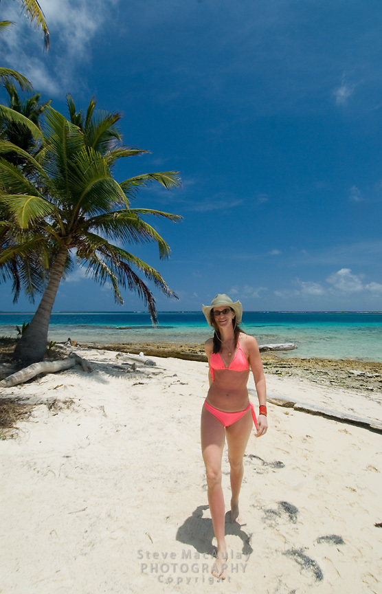 Woman strolls down the  white sand beach of Kuanidup Chico, Comarca De Kuna Yala, San Blas Islands, Panama