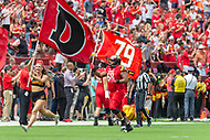 Landover, MD - September 1, 2018: Maryland Terrapins offensive lineman Ellis McKennie (68) leads the Terps onto the field carrying a flag for fallen teammate Jordan McNair before game between Maryland and No. 23 ranked Texas at FedEx Field in Landover, MD. The Terrapins upset the Longhorns in back to back season openers with a 34-29 win. (Photo by Phillip Peters/Media Images International)