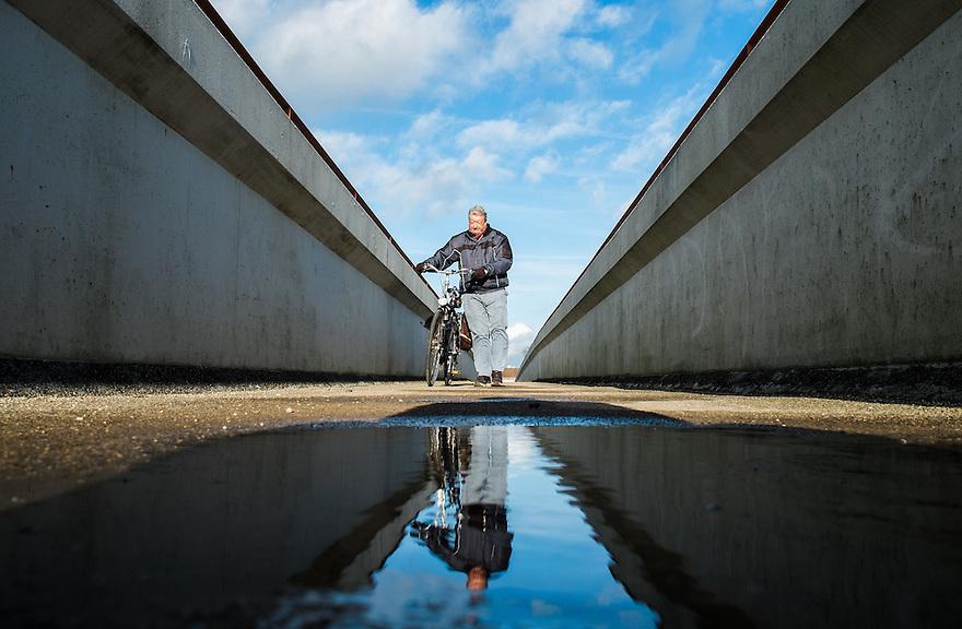 Nederland, Bunnik, 10 jan 2014<br /> A 12 bij Bunnik. Oudere man loopt over een voetgangersbrug over de A12<br /> <br /> Foto: Michiel Wijnbergh