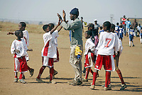SOWETO, SOUTH AFRICA - SEPTEMBER 15: Unidentified boys celebrate with their coach after winning a soccer a game on September 15, 2007 in the Jabulani section Soweto, South Africa. Soccer is the most popular sport in South Africa, and a because of the upcoming World Cup 2010 in South Africa the interest is increasing. For the first time the World Cup will be held on the African continent. South Africa doesn't have an organized youth soccer program and many teams and players struggle with lack of funds, to buy equipment and money for transport to games. (Photo by Per-Anders Pettersson)....