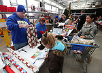 Volunteers wrap gifts at the 10th annual Holiday with a Hero event at Walmart in Carson City, Nev., on Wednesday, Dec. 17, 2014. The event pairs 200 of Carson City's K-5th grade homeless students with a local heroes for Christmas shopping. <br />