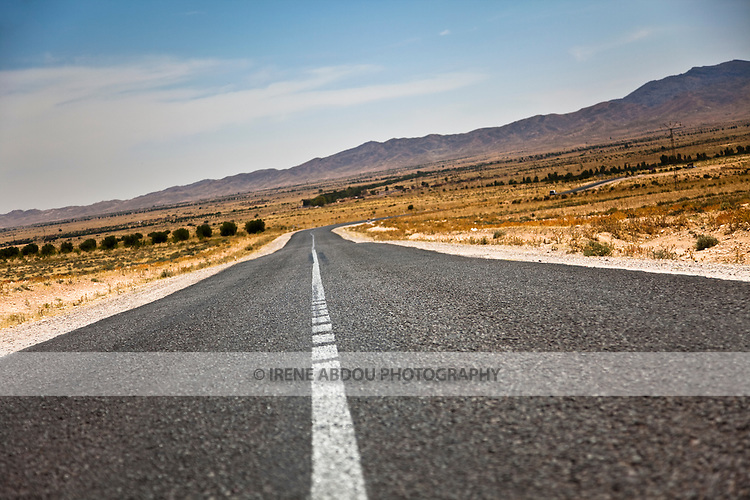 The highway from  Kasserine to Tozeur in Central Tunisia stretches onwards in isolation, reaching out to the ever-distant mountains on the horizon.