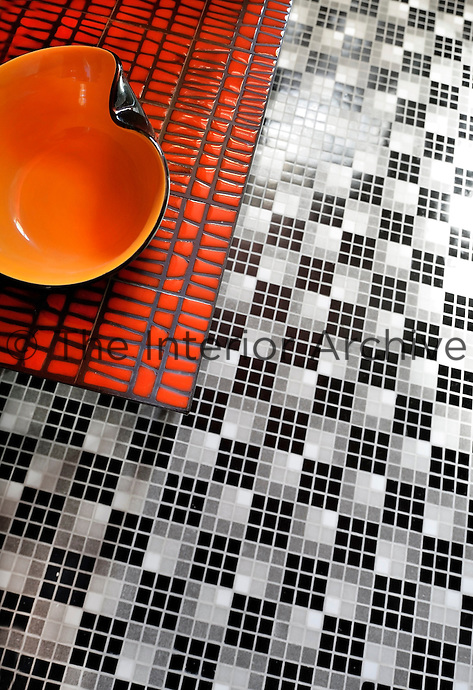 Bisazza glass mosaic tiles in a black and white geometric pattern contrast with a ceramic table in the bathroom