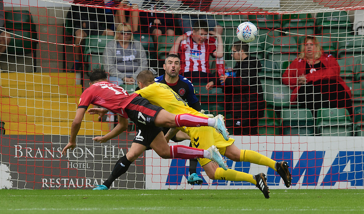Lincoln City's Tyler Walker scores the opening goal, beating Fleetwood Town's Matt Gilks with a diving header<br /> <br /> Photographer Chris Vaughan/CameraSport<br /> <br /> The EFL Sky Bet League One - Lincoln City v Fleetwood Town - Saturday 31st August 2019 - Sincil Bank - Lincoln<br /> <br /> World Copyright © 2019 CameraSport. All rights reserved. 43 Linden Ave. Countesthorpe. Leicester. England. LE8 5PG - Tel: +44 (0) 116 277 4147 - admin@camerasport.com - www.camerasport.com