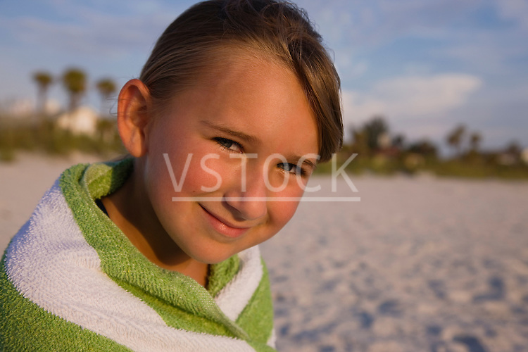 USA, Florida, St. Pete Beach, girl (8-9) wrapped in towel sitting on beach