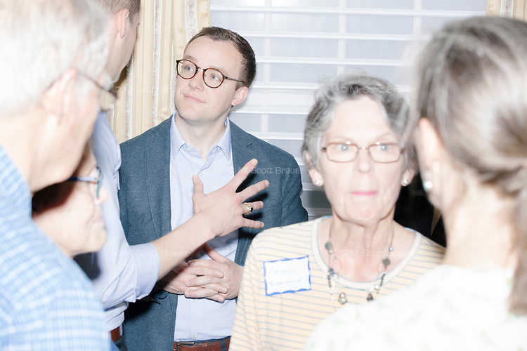 Chasten Buttigieg speaks with people after his husband Democratic presidential candidate and South Bend mayor Pete Buttigieg spoke at a house party with the Bedford Democrats in Bedford, New Hampshire, on Sat., Apr. 20, 2019. The candidate stood on a chair throughout his speech.