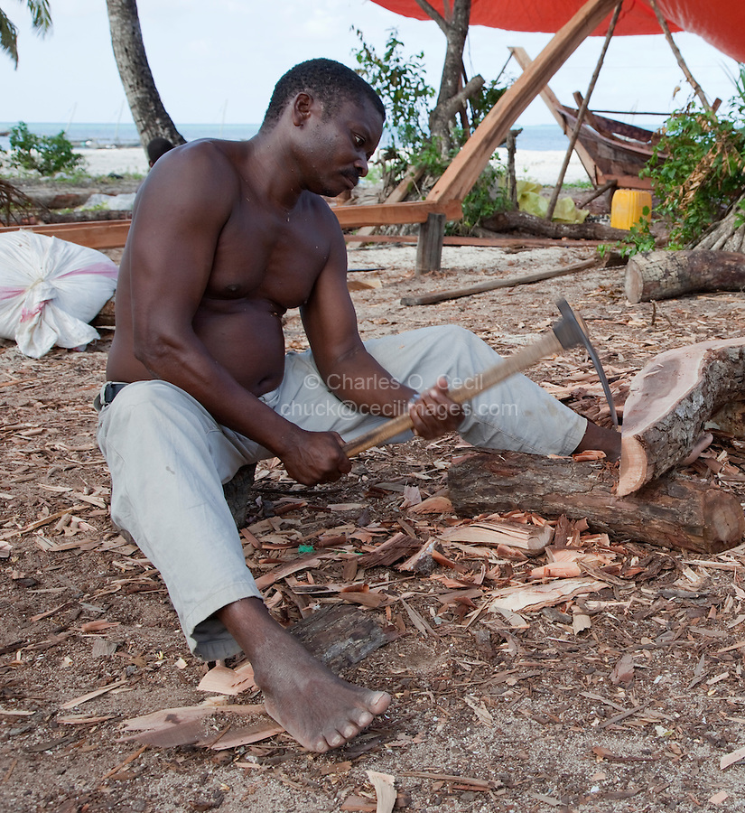 Nungwi, Zanzibar, Tanzania.  Dhow Construction, Boat Building.  Carpenter using an adze to shape the end of a log.