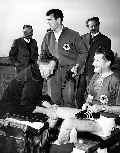 Fritz Walter (R, bottom), is tended by the masseur Erich Deuser (L, front) while forward Hans Schaefer (C) hands him his second soccer boot at a training match during the 1962 Soccer World Cup in Chile, 8 June 1962. Fritz Walter who was no longer active in 1962, had been team captain and forward of the German national soccer team in 1954. He worked as a journalist during the 1962 World Cup.