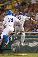 UCLA's Cody Regis runs into TCU pitcher Caleb Merck during a close play at first late  in Game 6 of the NCAA Division One Men's College World Series on Monday June 21st, 2010 at Johnny Rosenblatt Stadium in Omaha, Nebraska.  (Photo by Andrew Woolley / Four Seam Images)