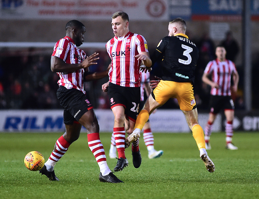 Lincoln City's John Akinde, left, and Harry Anderson battles with Newport County's Dan Butler<br /> <br /> Photographer Andrew Vaughan/CameraSport<br /> <br /> The EFL Sky Bet League Two - Lincoln City v Newport County - Saturday 22nd December 201 - Sincil Bank - Lincoln<br /> <br /> World Copyright © 2018 CameraSport. All rights reserved. 43 Linden Ave. Countesthorpe. Leicester. England. LE8 5PG - Tel: +44 (0) 116 277 4147 - admin@camerasport.com - www.camerasport.com
