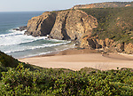 Sandy Carvalhal beach in bay between rocky headlands at Parque Natural do Sudoeste Alentejano e Costa Vicentina, Costa Vicentina natural park, near Brejão, south west Alentejo, Alentejo Littoral, Portugal, Southern Europe