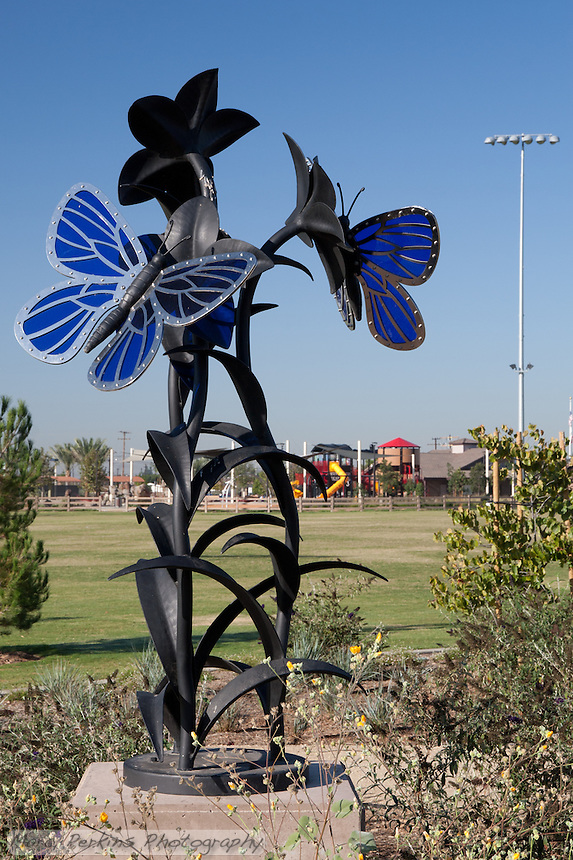 The butterfly statue at Stanton Central Park, seen on a clear sunny day with the iconic train play structure and baseball field lights visible in the background.  The statue is made of blue glass, stainless steel, and black iron.
