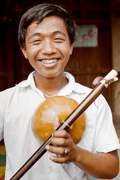 A portrait of a young Cambodian music student holding his Kse Diev. ( instrument )...Cambodian Living Arts works to support the revival of traditional Khmer performing arts and to inspire contemporary artistic expression. CLA supports arts education, mentorship, networking opportunities, education, career development, and income generating projects for master performing artists who survived the Khmer Rouge as well as the next generation of student artists.