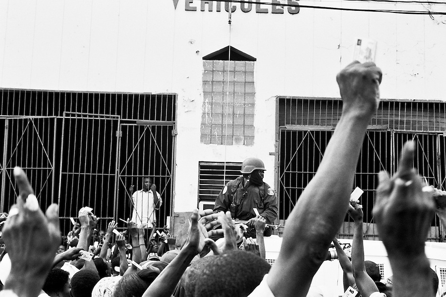 Haitians chanting and waiving voter ID cards in the air demanding access to the voting station.