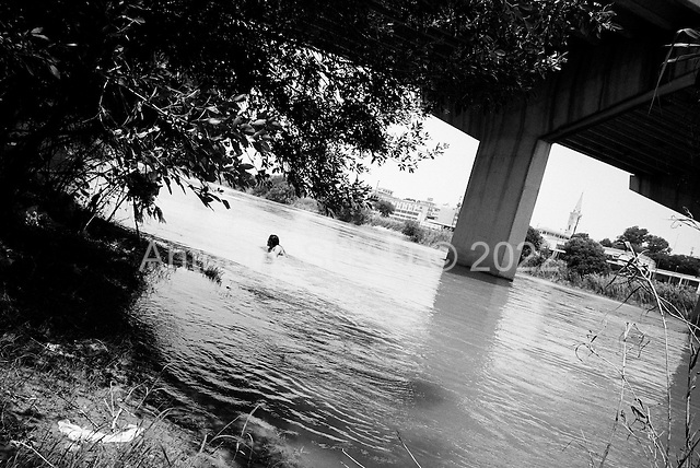 Nuevo Laredo, Tamaulipas<br /> Mexico<br /> June 7, 2007<br /> <br /> Mexicans and coyotes cross the R&iacute;o Bravo river here into the USA. People swim in the river at a parks as US border patrol watches through binoculars in the trees across the river. Many coyotes (people who lead others across for a fee) cross here with people and sometimes people come to swim with families and then just slip across the river.