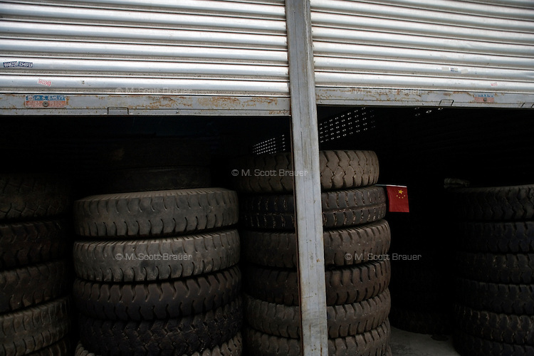 A stack of tires stand in a small warehouse with a Chinese flag in Mianyang, Sichuan Province, China.