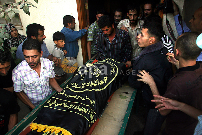 Palestinians carry the body of Abdullah Maqawai during his funeral in Rafah in the southern Gaza Strip on October 8, 2012 after he died of his wounds sustained in an Israeli air strike. Gaza's ruling Hamas movement and the Islamic Jihad group fired a barrage of projectiles at Israel, a day after a targeted Israeli air strike on the Palestinian enclave. Photo by Eyad Al Baba