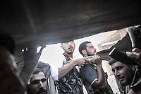 Opposition fighters drive away from the industrial neighborhood of Holok which is under heavy shelling by Syrian army aircraft and helicopter in the north of Aleppo City.