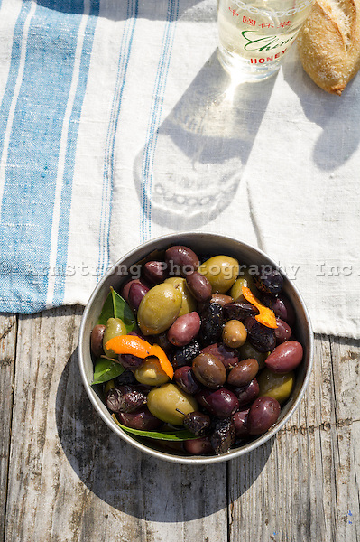 A bowl of mixed olives (black, green, kalamata), on a picnic table. With tablecloth, baguette, and a beverage