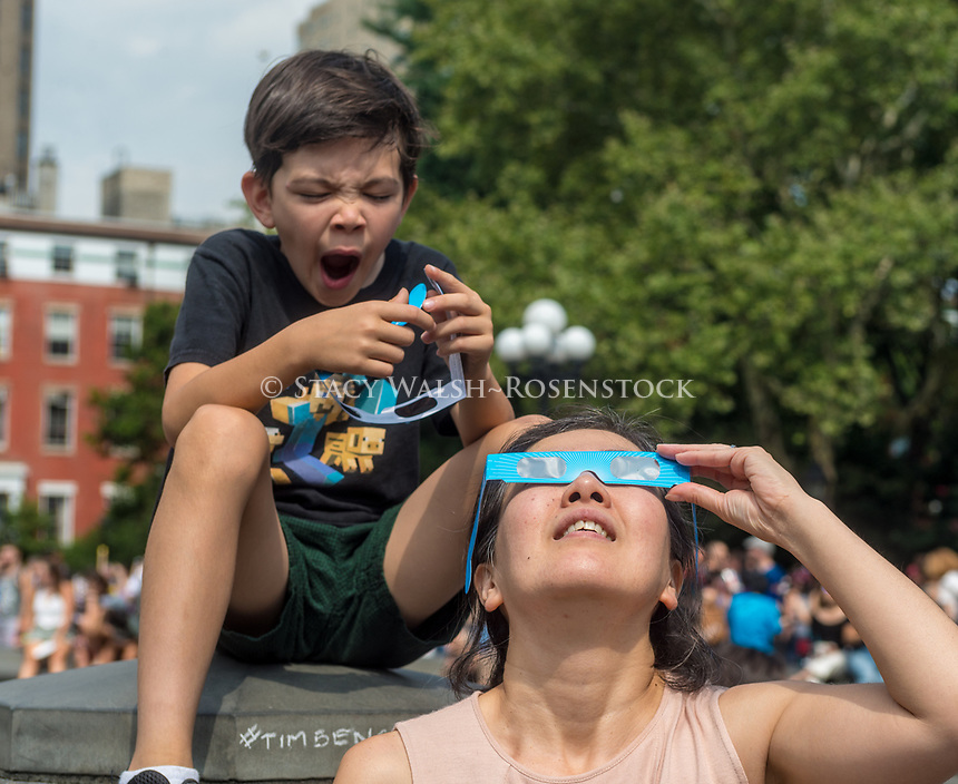 New York, NY 21 August 2017 - As mom watches the eclipse a young boys grows impatient. New Yorkers gathered in Washington Square to see a partial solar eclipse. ©Stacy Walsh Rosenstock
