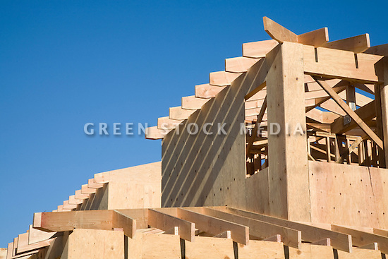 Wood roof joists line the first and second story roofs of a new house under construction below a clear blue sky.