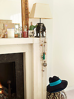 A small lamp on the narrow mantelpiece surrounding the fireplace in the master bedroom displays a collection of necklaces