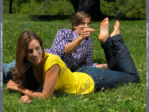 Young happy couple in their early thirties having fun in the nature on green grass. Young man tickling laughing young woman's bare feet.
